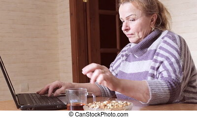 Grandma chatting behind the laptop while sitting in the kitchen