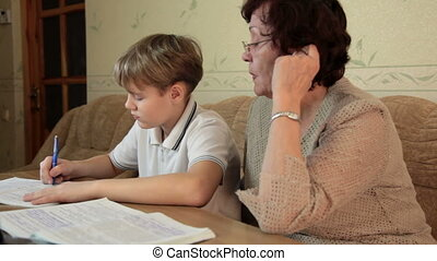 Grandma helping her grandson doing homework sitting at a desk in the living room
