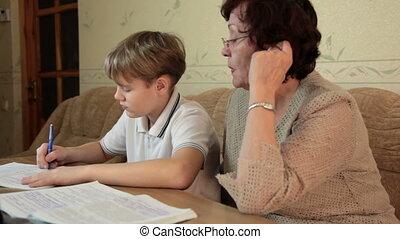 Grandma helping her grandson doing homework sitting at a desk in the living room