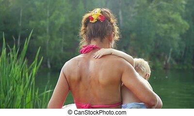 Grandma holds grandson go swimming in a lake in sunny day in...
