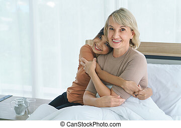 Grandma hugs granddaughter and smiling happily