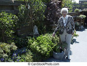 grandma in the garden - granma shwoing her garden with...