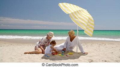Grandma Mom and Little Girl Playing at Beach Sand - Grandma...