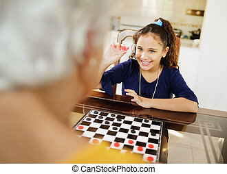 Grandma Playing Checkers Board Game With Granddaughter At Home