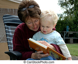 Grandma reading a book for her grandchild, both enjoying and having a good (learning) time.