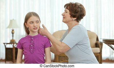 Granny affectionately combing her granddaughter%u2019s hair