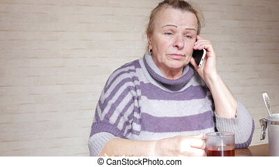 Grandma talking on phone sitting at the kitchen table