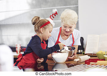 Grandma teaching her grandchild how to make a cake