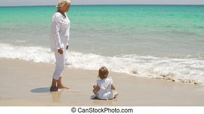 Grandma Watching Over her Little Girl at the Beach - Loving...