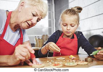 Grandma with girl applying icing on cookies