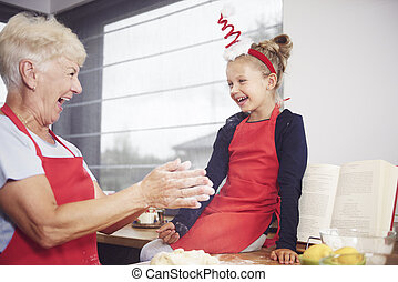 Grandma with girl enjoying in kitchen