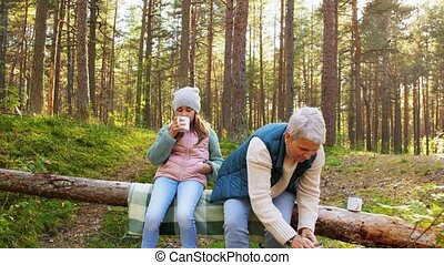 picking season, leisure and people concept - grandmother and granddaughter having picnic and drinking tea in autumn forest