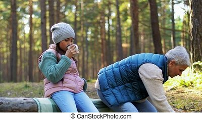 grandma with granddaughter drinking tea in forest - picking ...