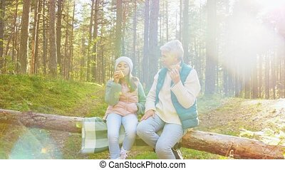 grandma with granddaughter having picnic in forest - picking...