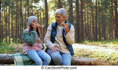 picking season, leisure and people concept - grandmother and granddaughter having picnic and eating pie in autumn forest