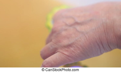 Grandma With Rattle In Hand, Close-up.