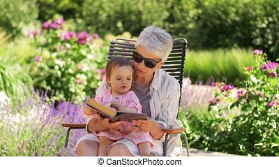 family, generation and people concept - happy grandmother with baby granddaughter reading book at summer garden