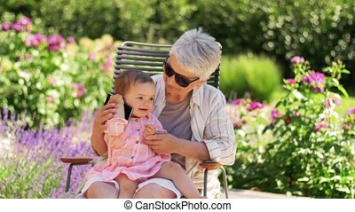 family, generation and people concept - happy grandmother with baby granddaughter calling on smartphone at summer garden