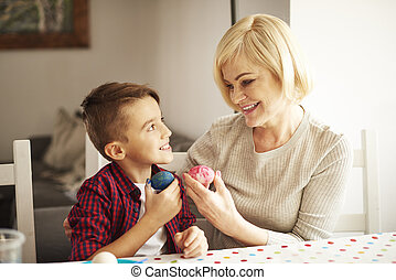 Grandmother and cute boy with painted eggs