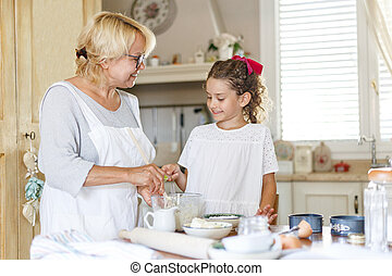 Grandmother and cute little curly granddaughter in the kitchen, they are preparing together.
