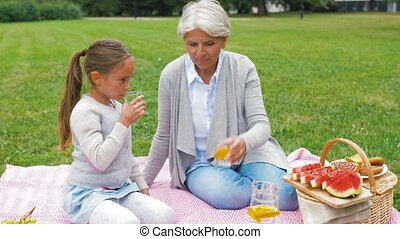 grandmother and granddaughter at picnic in park - family,...