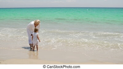 Grandmother and granddaughter at the seaside standing...