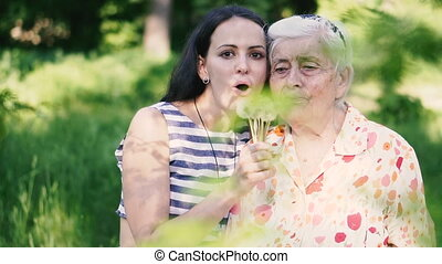 Grandmother and granddaughter blow dandelion