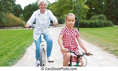 grandmother and granddaughter cycling at park - family,...