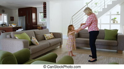 Grandmother and granddaughter dancing in living room 4k - ...