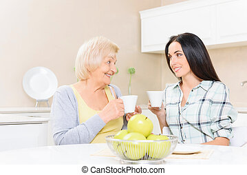 Grandmother and granddaughter drinking tea - Soft glance. ...