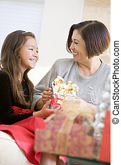 Grandmother And Granddaughter Exchanging Christmas Gifts