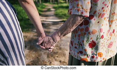 Grandmother and granddaughter hold hands and walk in the park