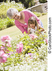 Grandmother and granddaughter outdoors in garden smiling