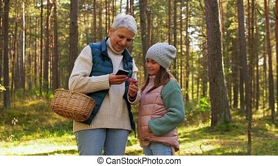 picking season, leisure and people concept - grandmother and granddaughter with baskets and smartphone using mobile app for mushrooms identification in forest