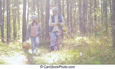 picking season, leisure and people concept - grandmother and granddaughter with baskets and mushrooms walking in forest