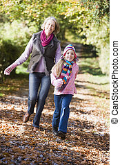 Grandmother and granddaughter running outdoors in park and smiling