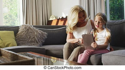 Caucasian girl at home, sitting on a couch with her grandmother, holding and using a digital tablet, social distancing and self isolation in quarantine lockdown during coronavirus covid19 epidemic