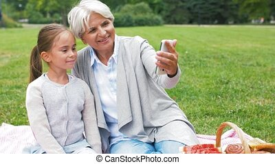 grandmother and granddaughter take selfie at park - family,...