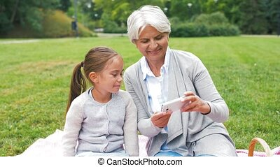grandmother and granddaughter take selfie at park