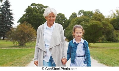 grandmother and granddaughter walking at park - family,...