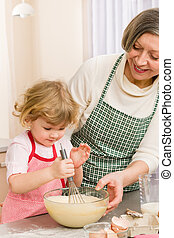 Grandmother and granddaughter whisk dough - Grandmother and...