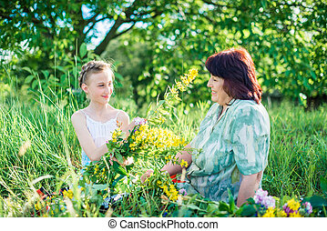 Grandmother and granddaughter with flowers