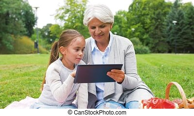 grandmother and granddaughter with tablet at park - family,...