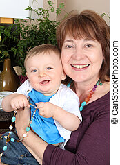 Grandmother and grandson - Beautiful baby boy sitting by his...