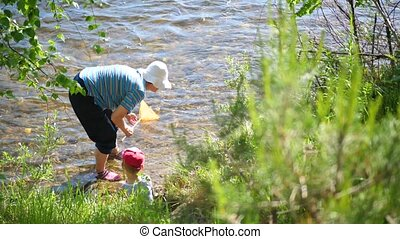 Grandmother and grandson fishing net. Coast of a mountain river. Cool water on a hot summer day