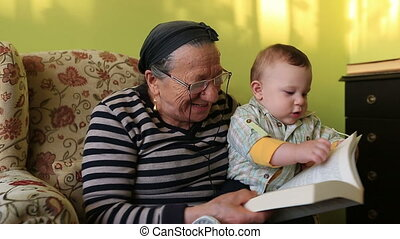 grandmother and grandson - grandmother reading a book to...