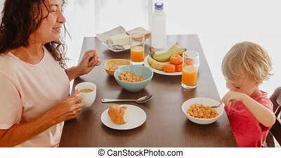 Grandmother and grandson have breakfast in the morning at...