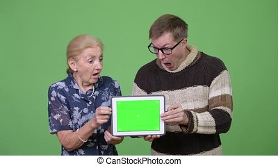 Grandmother and grandson showing digital tablet and looking shocked together