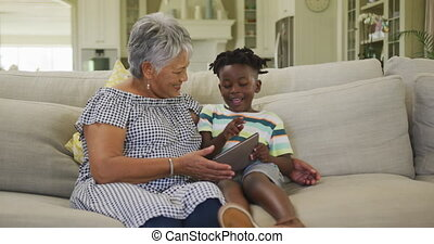 Grandmother and grandson using digital tablet at home - ...