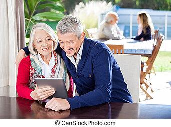 Grandmother And Grandson Using Digital Tablet At Nursing Home